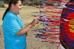 Young adult standing at a target that is full of arrows