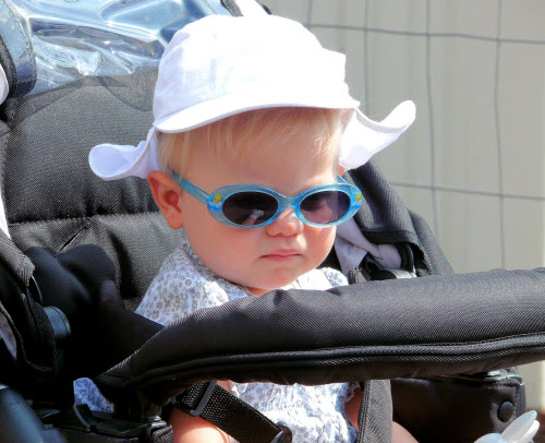 Young child in stroller wearing sunglasses