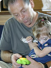 young daughter sitting on father's lap, playing with toy