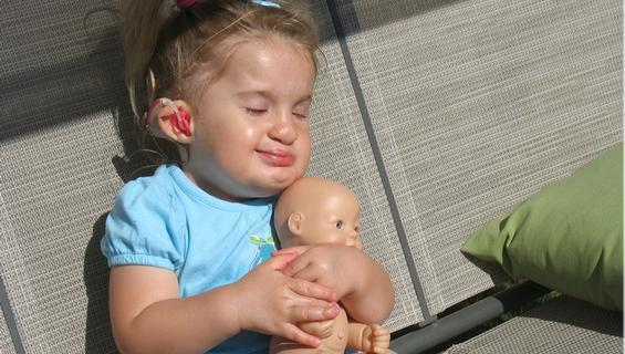 young girl sitting in sunshine holding toy doll