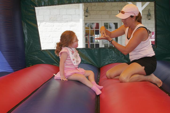 A woman signing to a child in a bouncehouse